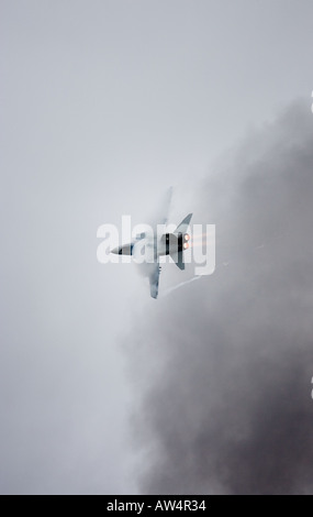 Tornado GR4 fighter jet with vapour trail flying through bomb smoke - Stock Photo