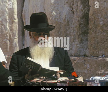 An Orthodox jew prays and reads from the torah at the Western or Wailing wall - Stock Photo