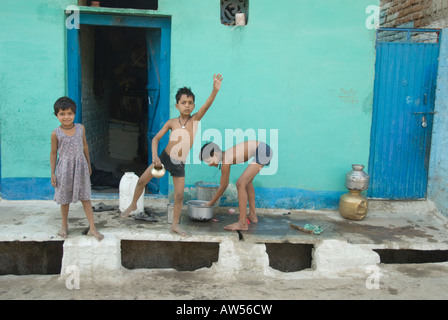 Children waving and bathing in front of their home in rural India - Stock Photo