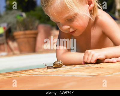 Little girl looking at a snail. - Stock Photo