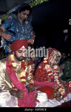 Sikh wedding nuptials with  bride and groom, marriage in a British gurdwara. - Stock Photo