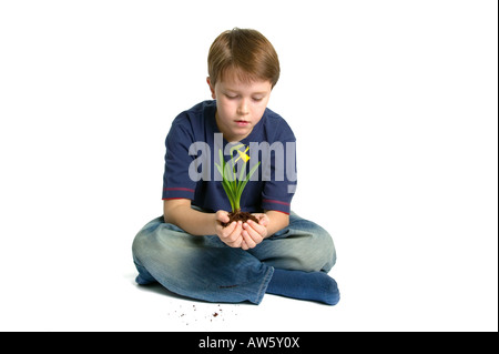 A young boy sat crossed legs holding a new daffodil in his hands shot against a white background - Stock Photo