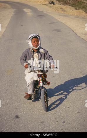 A young Palestinian boy on an old bicycle near the city of Jericho - Stock Photo