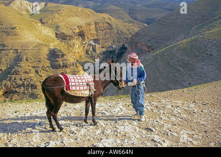 A young Arab boy with his donkey in front of the St Georges Monastery in the Judean Wilderness near Jericho - Stock Photo