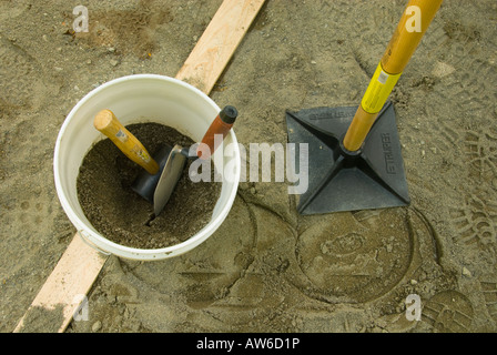 bucket with rubber hammer sand and spade stamper next to for brick patio laying - Stock Photo