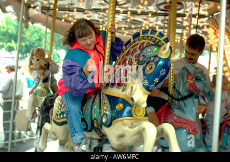 Down syndrome woman age 32 giving thumbs up on carousel. St Paul Minnesota USA - Stock Photo