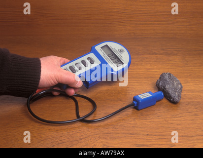geiger counter measuring the radioactivity of a rock sample - Stock Photo