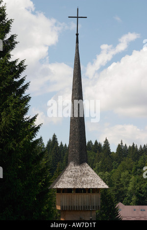 Wooden church roof with crucifix in the forest Poiana Brasov Kronstadt Romania - Stock Photo