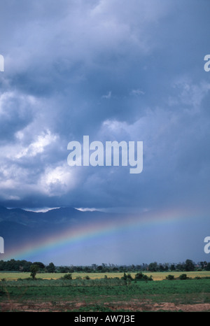 A rainbow falls over the plains of central Myanmar - Stock Photo