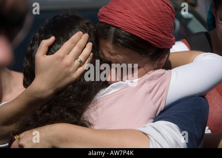 Religious Jewish women embrace each other during funeral of a terror victim in Jerusalem Israel - Stock Photo