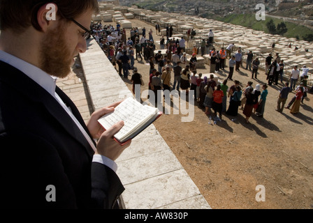An ultra orthodox Jewish man praying at a Jewish funeral at the Mount of Olives Jewish cemetery in East Jerusalem, - Stock Photo