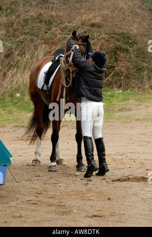 a horse rider putting on a head collar and making final adjustments to bit and tack before competition show jumping - Stock Photo