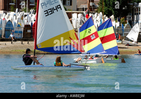 a flotilla of small sailing dinghies ata sailing club hardway for kids and children at gosport portsmouth hampshire - Stock Photo