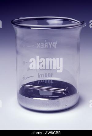 An iron nail floating on mercury - Stock Photo