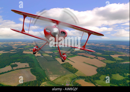 A red stunt biplane in flight over rural countryside - Stock Photo