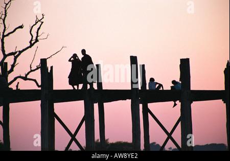 Monks and children at sunset on U Bein's Bridge, Amarapura, Myanmar (Burma) - Stock Photo