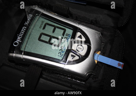 Diabetes Diabetic blood sugar glucose meter with blood applied for the test and the blood sugar 'slightly high' - Stock Photo