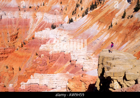 Hiker looking down on the colorful Cedar Breaks Amphitheater Cedar Breaks National Monument Utah - Stock Photo