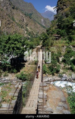 Crossing a rickety bridge over a river, Annapurna, Nepal - Stock Photo