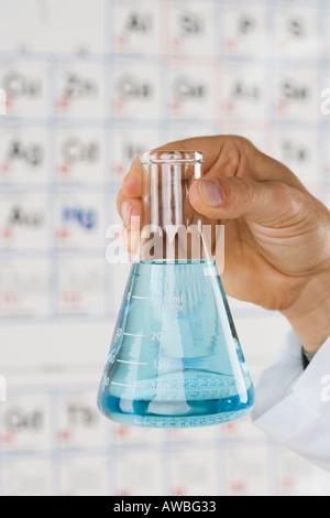 Hand holding beaker with liquid - Stock Photo