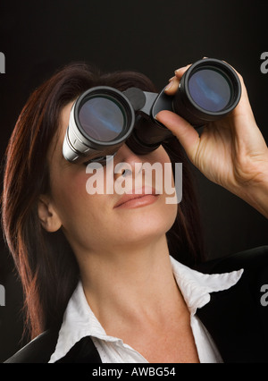 A businesswoman looking through binoculars, seeing ...