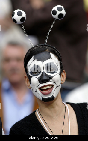 A supporter with a face painted as a football in the crowd during the 2006 World Cup - Stock Photo
