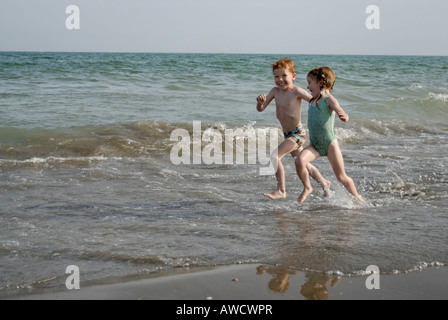 Mr two children are running at the beach - Stock Photo