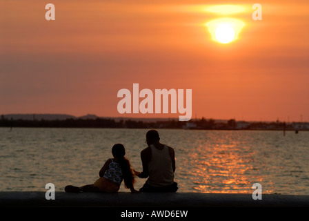 Man and child sitting on the malecón at sunset, Cienfuegos, Cuba, Americas - Stock Photo