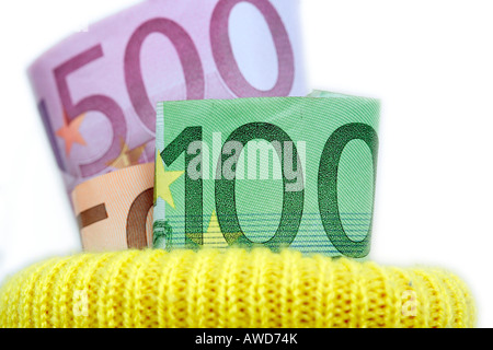 Saving money - Euro bank notes put into a yellow sock deposit - Stock Photo