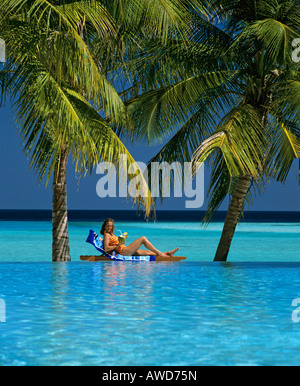 Young woman holding drink, laying on deck chair, swimming pool, ocean and palm trees, Sun Island, Ari Atoll, Maldives, - Stock Photo