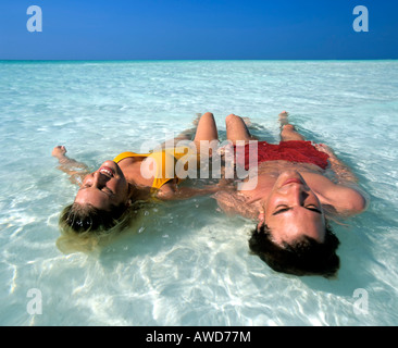 Young couple relaxing in shallow water, beach, Maldives, Indian Ocean - Stock Photo