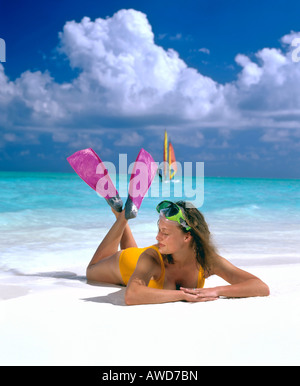 Young woman laying on beach with snorkeling gear, windsurfer at the back, Maldives, Indian Ocean - Stock Photo