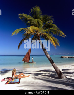 Palm tree, girl tanning on beach, boat with red sail, Maldives, Indian Ocean - Stock Photo