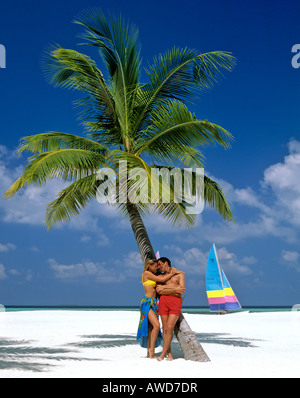 Palm tree, young couple hugging on the beach, catamaran, Maldives, Indian Ocean - Stock Photo