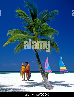 Palm tree, young couple on the beach with snorkeling gear, catamarans, Maldives, Indian Ocean - Stock Photo