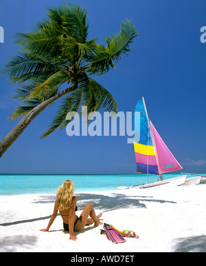 Young woman with snorkeling gear on sandy beach, catamaran and palm tree, Maldives, Indian Ocean - Stock Photo