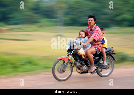 Man and sons on a motorcycle in rural Laos - Stock Photo
