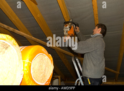 Carpenter working with chainsaw at the roof truss - Stock Photo