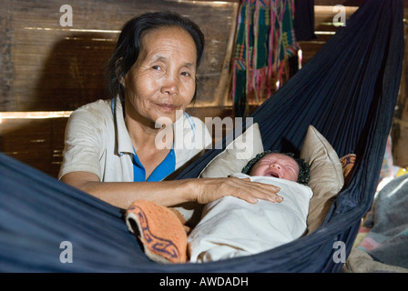 Midwive dandling baby in a hummock, refugee camp Ei Tu Hta, IDP-Area bordering Thailand near Mae Sariang, Birma - Stock Photo
