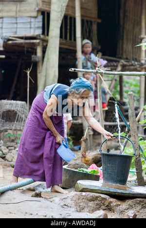 Old woman collecting water at the source, refugee camp Ei Tu Hta, IDP-Area bordering Thailand near Mae Sariang, - Stock Photo
