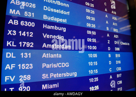 Blue screen with list of flights and city names at an airport - Stock Photo