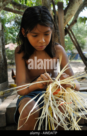 Girl lacing a basket of Tucuma palm fibers (Astrocaryum vulgare), Amazon Basin, Brazil - Stock Photo