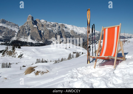 Chair and a pair of skis in front of the Sella group, Alta Badia ski area, Dolomites, Italy - Stock Photo