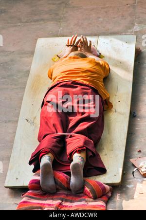 Monk praying in Bodhgaya at Mahabodhi Temple under the BodhiTree Bihar India - Stock Photo