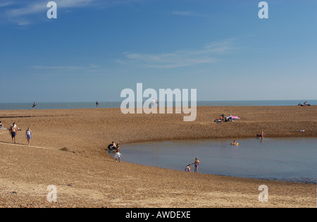 People bathing and walking in a water inlet at Old Felixtowe Beach on a fine summers day - Stock Photo
