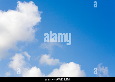 Fluffy white cumulus clouds in a blue sky indicating clement summer weather. England UK Britain - Stock Photo