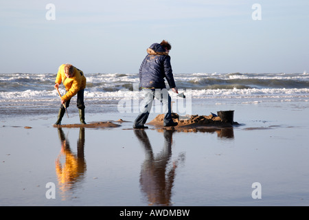 Boys building sand castle on the beach, Northsea, the Netherlands, Europe - Stock Photo
