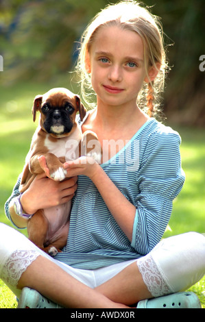 Royalty free photograph of young girl cuddling and loving her family puppy boxer dog in her garden at a house in - Stock Photo