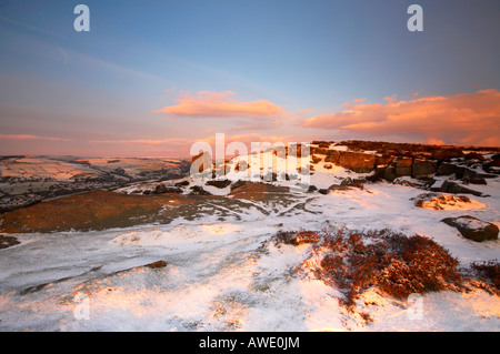 Winter scene at sunrise on a snow covered Curbar edge in Derbyshire Peak District - Stock Photo