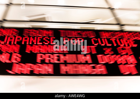 Scrolling digital neon sign in Tokyo street at night. Motion blur on pan as camera follows the phrase JAPANESE POP - Stock Photo